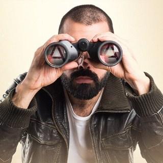 Man looks intensely through his binoculars