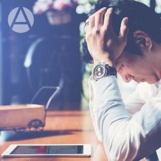 Man looks stressed over his ipad