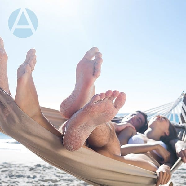 Happy couple naps together in a hammock on the beach