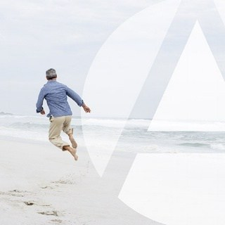 Man is very excited and clicks his heels mid-jump on the beach
