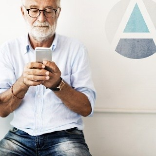 Older man works on his phone in casual attire