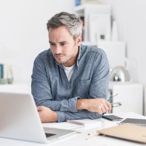 Man with pepper gray hair looks at his computer
