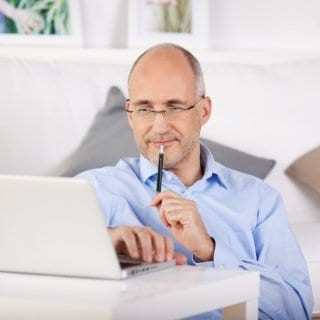 middle aged man looks intently at computer