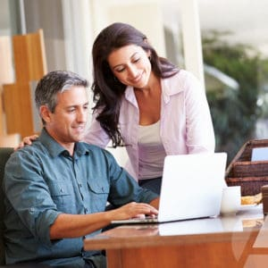 Couple reviews paperwork for Roth IRAs to assess the benefits for their retirement plan.