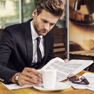 Younger man reads the newspaper while drinking coffee