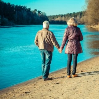 Older couple walks on the shore of a lake during fall