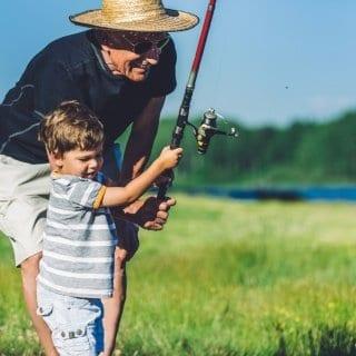 Grandpa helps little boy fish