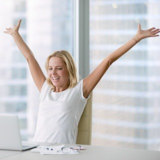 Woman looks excited at her computer