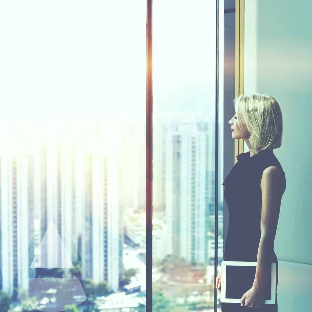 woman stares out of her office window in a downtown high rise