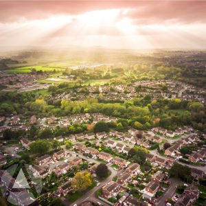 Aerial photo of the sun shining down on a neighborhood of homes, surrounded by lush vegetation depicting different types of assets in real estate IRAs