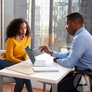An African American young woman in a bright yellow shirt sitting with an IRA professional at a conference table discussing the difference between self-directed IRAs vs. traditional IRAs.