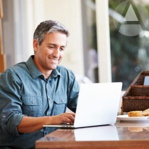 Middle aged man sitting at table on his laptop learning how to open a self-directed IRA.