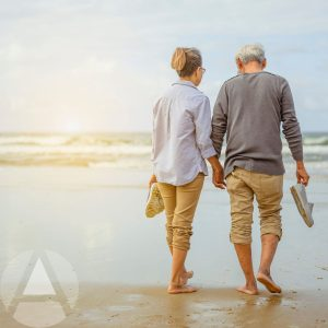 Retired couple walking in the sandy water on a beach at sunset enjoying retirement.