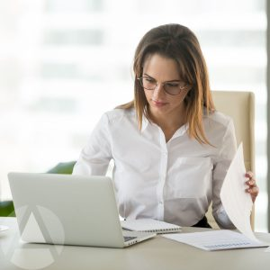 A pretty brown-haired woman sitting at a desk with her computer and papers reviewing the differences between Roth IRAs vs. traditional IRAs.