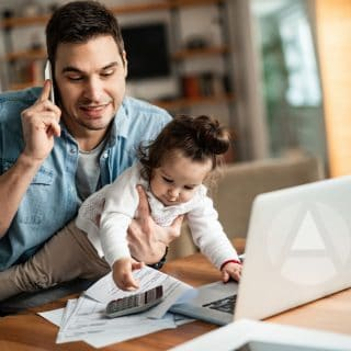 Dark-haired man sitting at a desk looking at a computer in his work-from-home rental, with his infant daughter in his lap and grabbing papers off the desk..