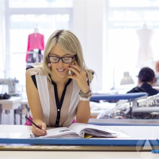 Pretty blonde female business owner at desk talking on the phone and smiling.