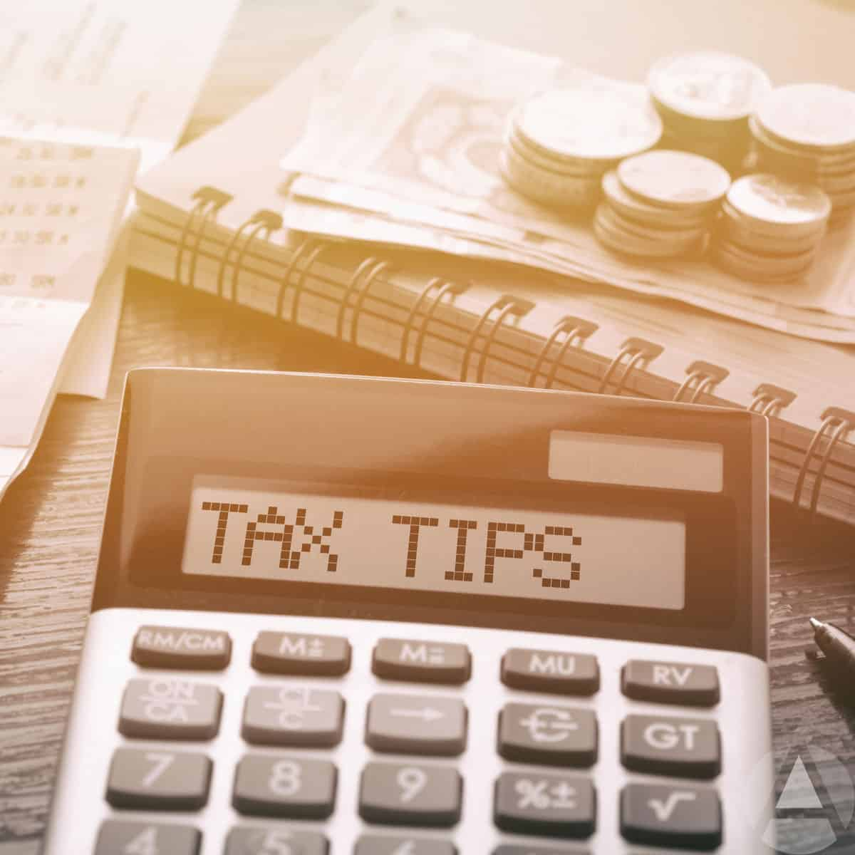 Calculator with money and a notebook to take notes on retirement planning tax strategies.