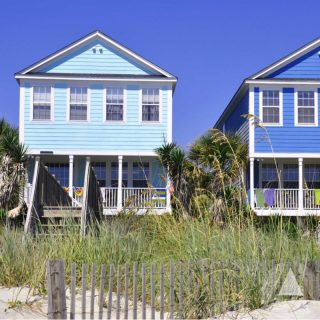 Colorful blue vacation rental investments on a grassy beach.