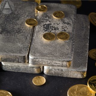 Silver bars and gold coins on a black surface representing assets for a precious metal IRA.