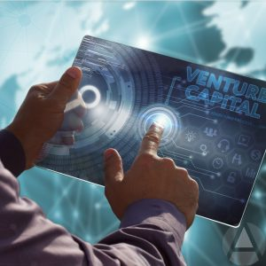 """Image of a man's hands holding a large blue card with the words """"venture capital"""" on it and a holograph image of the world behind the card."""