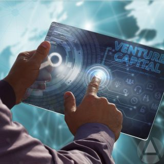 "Image of a man's hands holding a large blue card with the words ""venture capital"" on it and a holograph image of the world behind the card."
