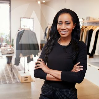 Young African American businesswoman standing in her clothing store, with light streaming through the windows behind her.