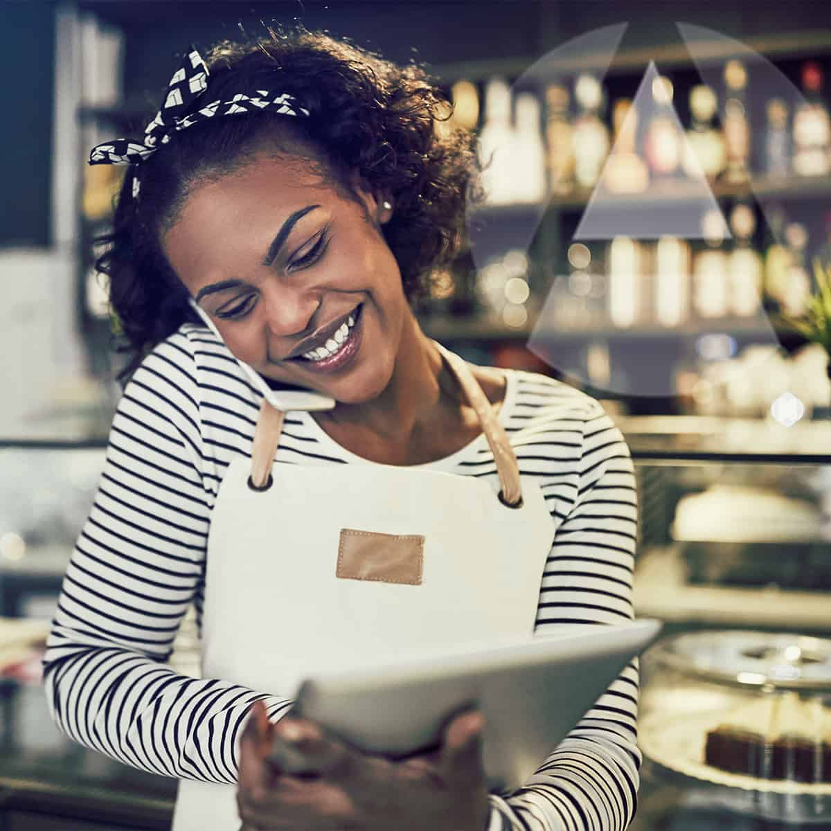 African American entrepreneur smiling while she looks at her iPad.