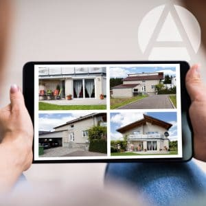 Investor searching for real estate on iPad with pictures of four houses for sale.