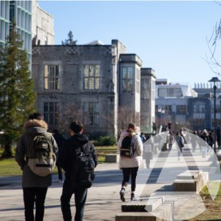 Students walking around on a university campus between classes in a location where rental property in a college town may be a good investment.