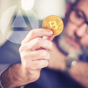 The hand of a white man holding a coin that symbolizes bitcoin investments, with the man in the background wearing glasses and appearing to consider bitcoin in his IRA.