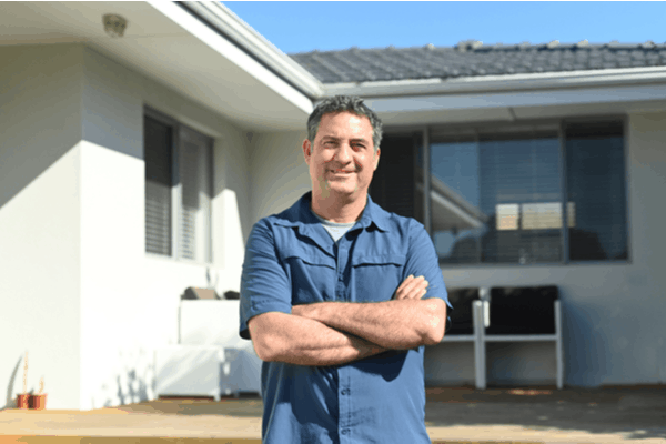 Man stands in front of his investment rental property